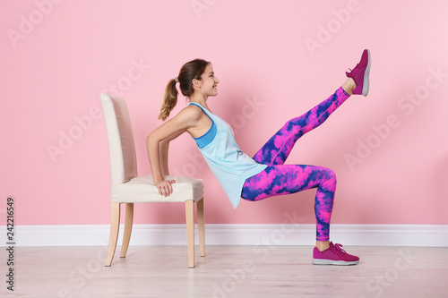 Young woman exercising with chair near color wall. Home fitness