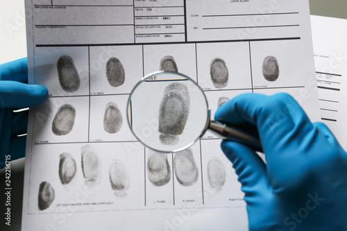 Criminalist exploring fingerprints with magnifying glass, closeup