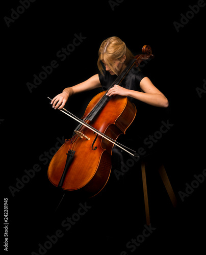 Canvastavla Young girl playing the cello on isolated black background