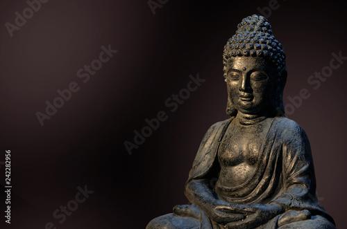 Buddha statue sitting in meditation pose against deep dark background.