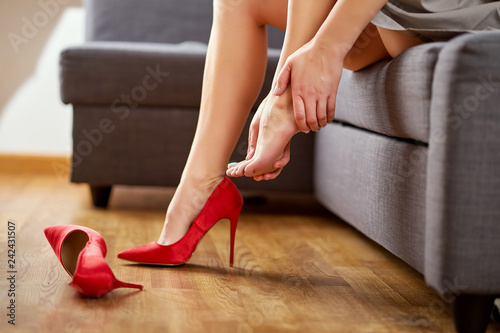Fototapeta Business Woman taking off sexy red high heels shoes after work and massages painful feet at home on gray couch