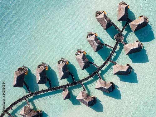 Stampa su Tela Luxury overwater villas with coconut palm trees, blue lagoon, white sandy beach