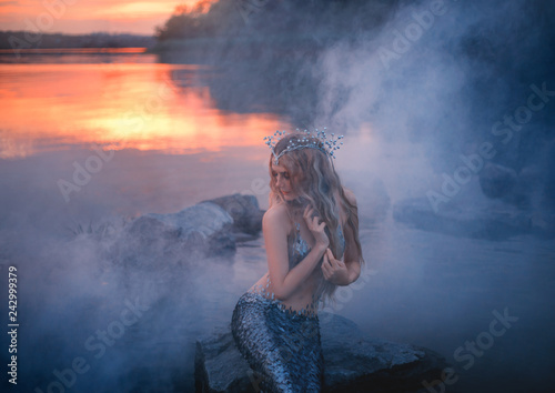 Carta da parati sea maiden with long blond hair, shell tiara sits in thick fog, combs her hair w