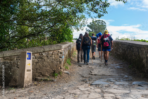 Canvas Print FURELOS, SPAIN - JULY 31, 2016: Some young pilgrims with backpacks cross a medieval bridge, making the Camino de Santiago