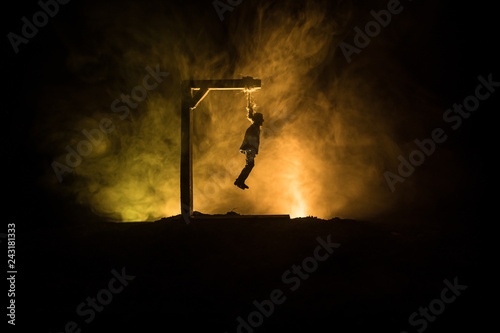 Fotografija Horror view silhouette of hanged man on scaffold at night with fog and toned light on background