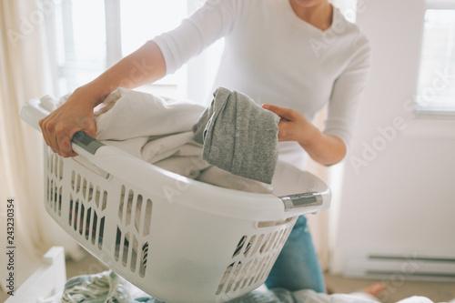 Fototapeta A woman folding laundry in a bright white bedroom.