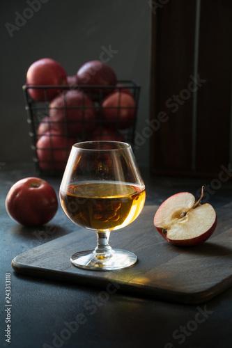 Obraz na plátne Glass with Calvados brandy and red apples on black.