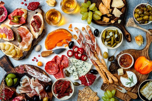 Appetizers table with antipasti snacks and wine in glasses. Brushetta or authentic traditional spanish tapas set, cheese and meat platter over grey concrete background. Top view