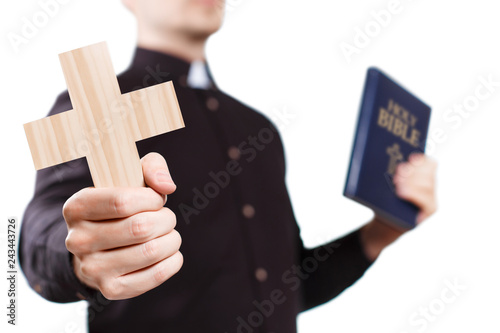 Valokuvatapetti Priest holding a cross and the Holy Bible, isolated on white background