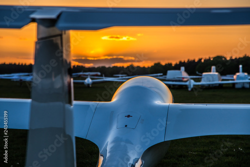 Segelflugzeuge stehen auf einem Flugfeld im Sonnenuntergang