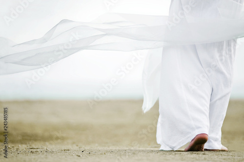 Photo Photo of a man walking in a white robe on the sand