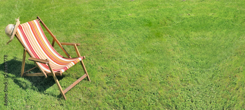 Fényképezés deckchair on greenery grass in a garden in panoramic size