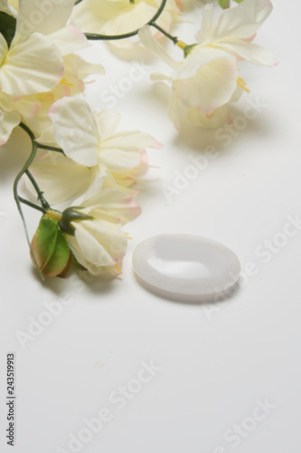 White flowers with a stone that depicts peace