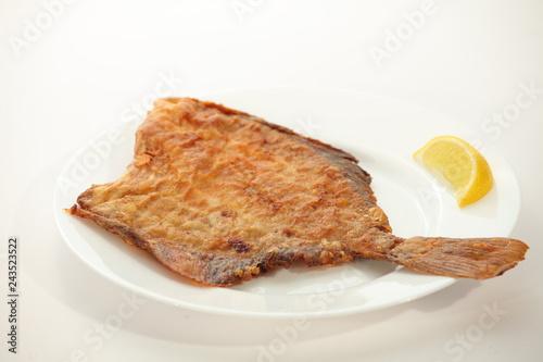 Fototapeta Fried flounder fish on white plate with lemon