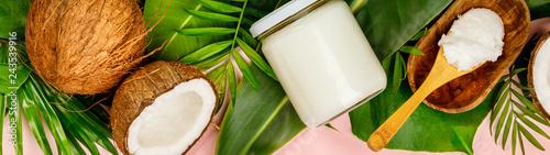 Fotografia Coconut oil, tropical leaves and fresh coconuts