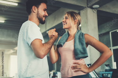 Attractive young couple handshaking after workout in fitness gym., Portrait of man and woman couple love are working out training together., Couple fitness and healthy concept.