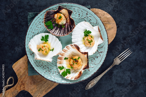 Photo Seared scallops shell with butter, garlic and parsley.