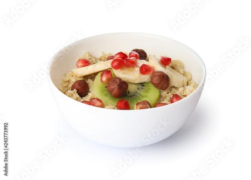 Bowl of quinoa porridge with hazelnuts, kiwi, banana and pomegranate seeds on white background