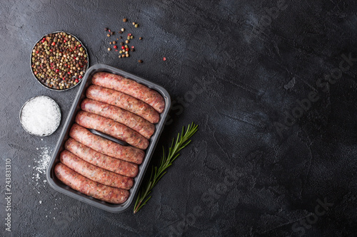 Raw beef and pork sausage in plastic tray with salt and pepper on black background. Space for text