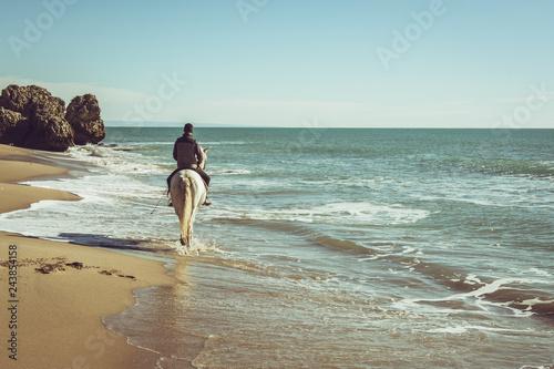 Fototapeta premium młody człowiek jeździć na białym koniu na plaży