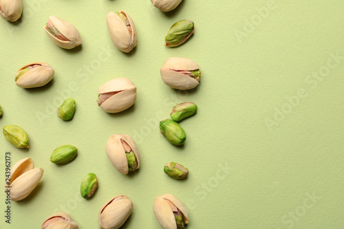 Organic pistachio nuts on color background, flat lay. Space for text