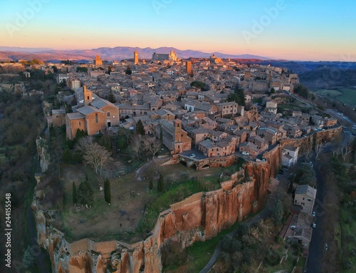 Fotografie, Tablou The last rays of sunlight hit the tall buildings not an Italian hilltop town