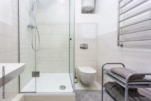 Fotografia toilet and detail of a corner shower cabin with wall mount shower attachment