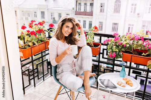 Stampa su Tela Attractive girl with long hair in pajama having breakfast on balcony in the morning in city