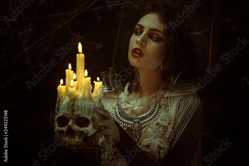 Photo candles in skull, vampire, demonic woman dressed in white lace and silver jewelry