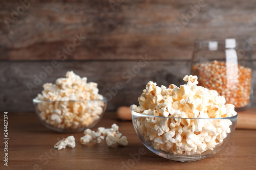 Glass bowl with tasty popcorn on table. Space for text