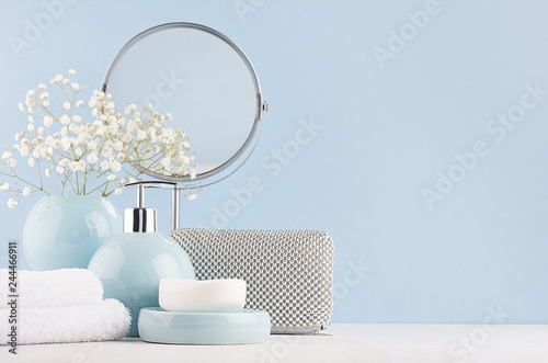 Valokuvatapetti Dressing table with circle mirror, cosmetic silver accessories and white small flowers in ceramic pastel blue vase on white wood board