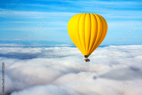 A lonely yellow hot air balloon floats above the clouds. Concept leader, success, loneliness, victory