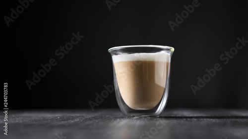 Fotografia A glass cup of hot flavored cappuccino presented on a black wooden table with copy space