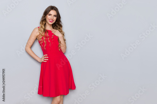 Beautiful Woman In Red Dress Is Holding Hand On Chest And Smiling Fototapeta