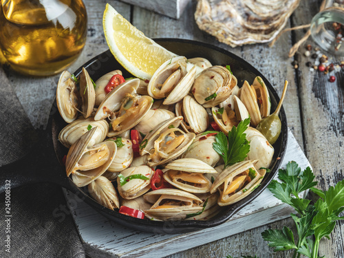 Cooked seafood clams in the iron pan portion with lemon and seasoning Fototapet