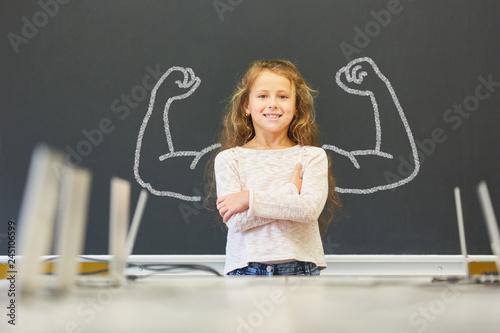 Fotografia Mädchen in Schule steht vor Tafel mit Muskeln