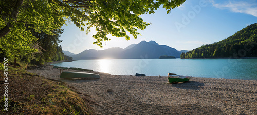 Canvas Print Malerische Bucht am Walchensee mit Fischerbooten und grünen Zweigen