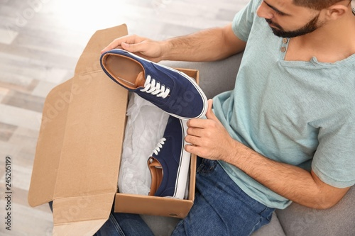 Young man opening parcel with shoes at home, closeup
