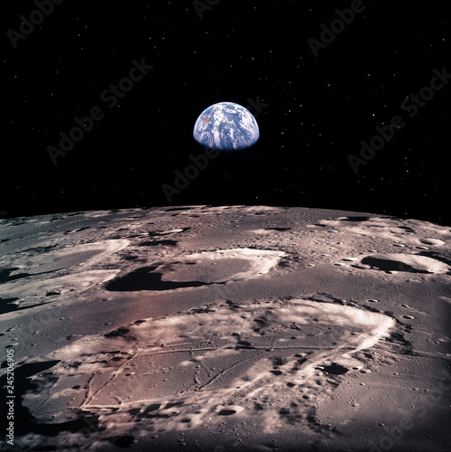 Earth rises above lunar horizon with huge meteor craters.  Elements of this image furnished by NASA.