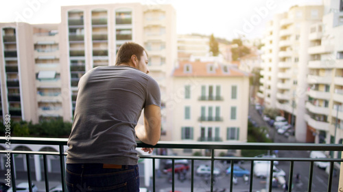 Fotografia Man enjoying view from his hotel suite balcony on busy street, business trip