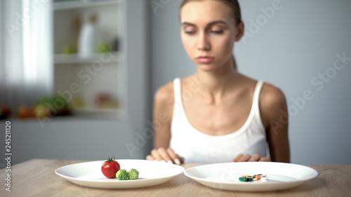 Fotografia Girl chooses vegetables instead of weight loss drugs, healthy diet, organic food