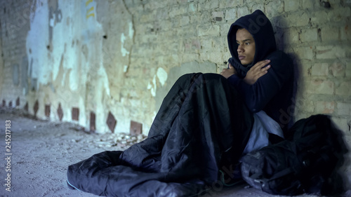 Valokuva Upset homeless teenager wearing hoodie, feeling cold, indifference and poverty