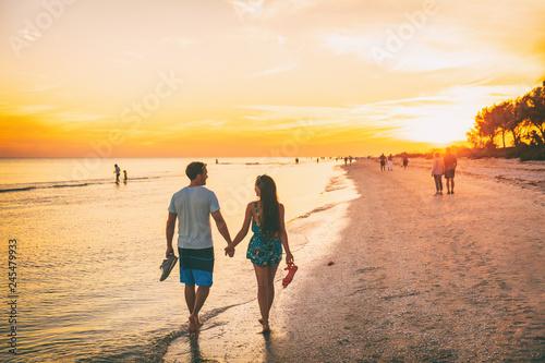 Beach summer beach people lifestyle happy couple enjoying sunset walk on Shelling beach famous tourist destination on the southwest coast of Florida -Gulf of Mexico. Sanibel Island, Florida.