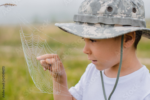 Stampa su Tela A little boy on the field is looking closely at a spider's web at sunrise in the fog