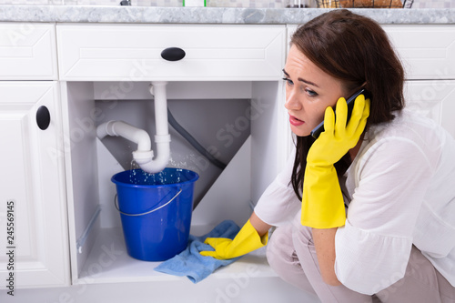 Fotografija Woman Calling Plumber In Front Of Water Leaking From Pipe