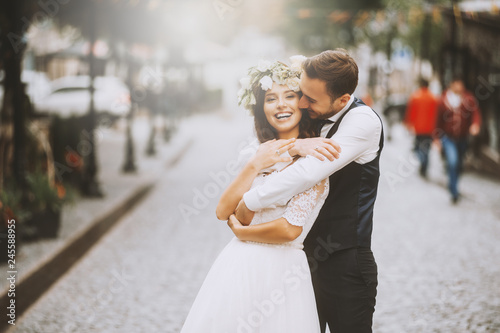 Foto Handsome loving couple, wife and husband, hugs tender his wife from back in the