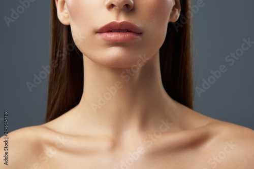 Fototapeta Young woman with beautiful full lips and graceful neck