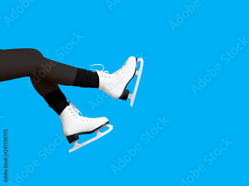Ice skating, skater, female feet in skates shoes isolated on blue background, ice rink. Winter time. Girl, winter sports, copy space