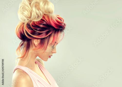 Piękna wzorcowa dziewczyna z elegancką wielo- barwioną fryzurą. Stylowa kobieta z podkreślając kolor włosów mody. Kreatywne czerwone i różowe korzenie, modna kolorystyka.