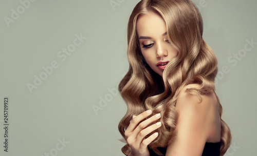 blonde girl with long  and   shiny wavy hair .  Beautiful  smiling woman model with curly hairstyle .